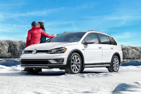 2018 Volkswagen Golf Alltrack parked in the snow with a couple leaning on it