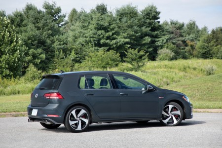 2018 Volkswagen Golf GTI driving down a wooded road