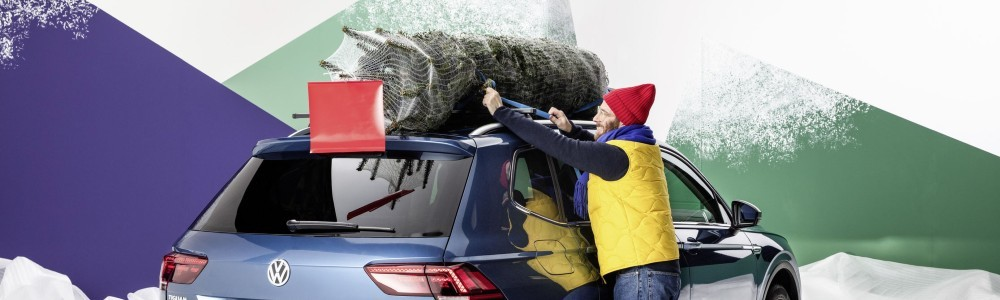 man putting a tree on a Volkswagen SUV