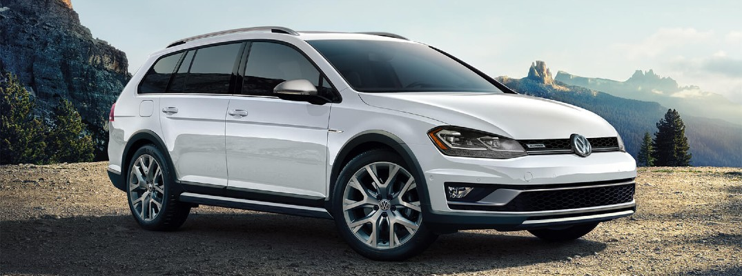 2020 Volkswagen Golf Alltrack white parked on mountain clearing with clouds in background