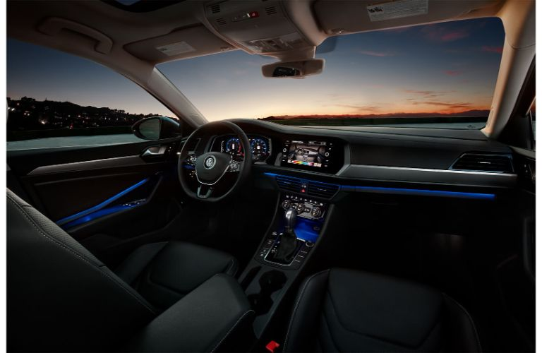 2020 Volkswagen Jetta SEL Premium interior shot showing blue accent lighting dashboard front driver seat and console with sunset through windshield