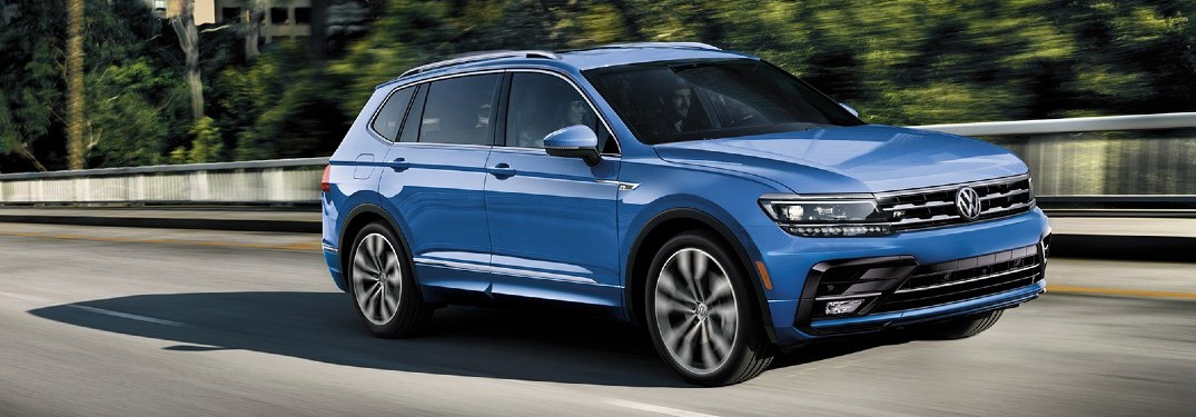 2020 VW Tiguan blue exterior driving to the right on railed road with trees in background