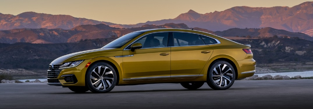 2020 Volkswagen Arteon 2019 shown mustard yellow in shadows driving in view of mountains