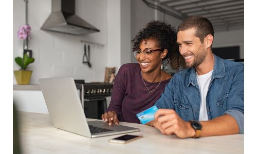 stock photo of couple shopping online with laptop holding credit card