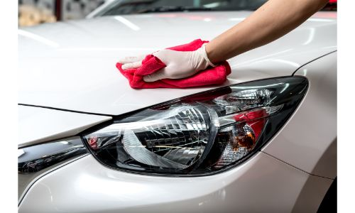 hand with glove drying white car with red rag