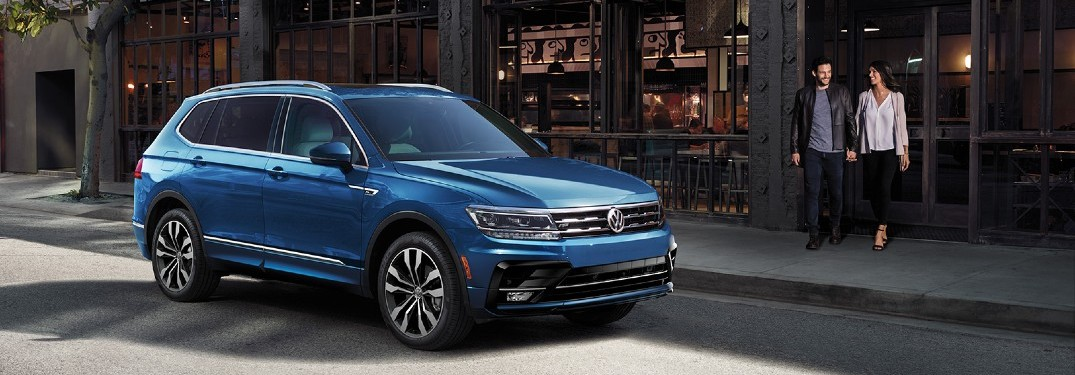2020 VW Tiguan blue parked outside business with couple walking toward