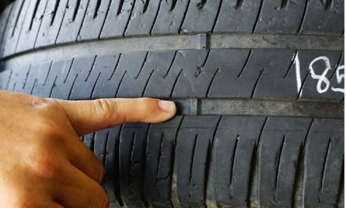 finger pointing at tire tread wear mark