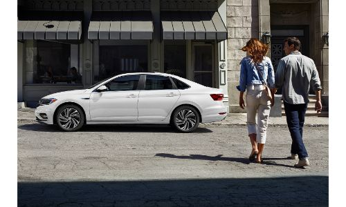 2020 VW Jetta white parked on street with couple walking toward