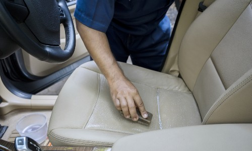 person cleaning leather car seat with sponge