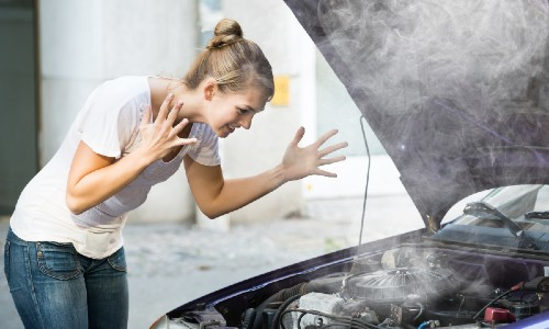 woman in white shirt and jeans stressed about overheated car