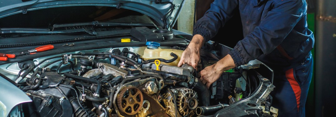 mechanic with dirty hands and blue jumpsuit reaching hands into car under hood