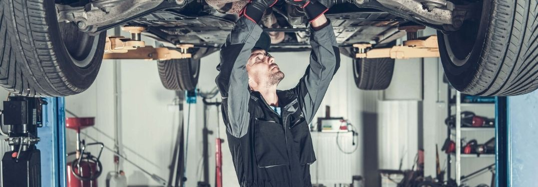 Image of an auto mechanic tending to a car