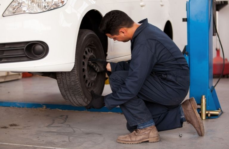 Image of an auto mechanic checking the tires