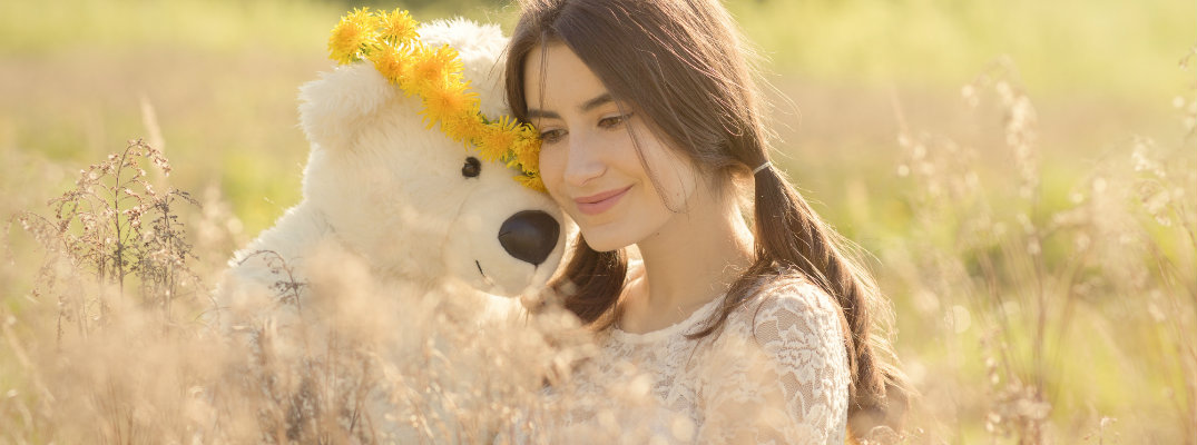 Girl in a field hugging a teddy bear