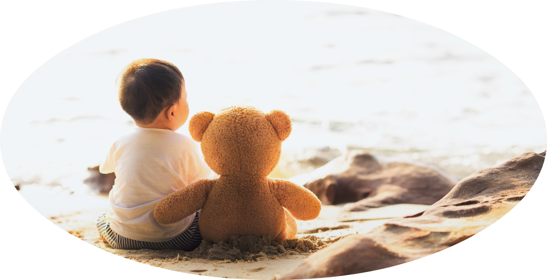 Little boy at the beach looking at the ocean with his teddy bear