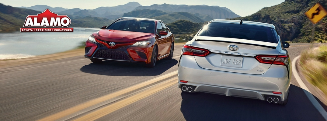 2018 Toyota Camry Red and Silver Exteriors on Highway with Alamo Toyota logo