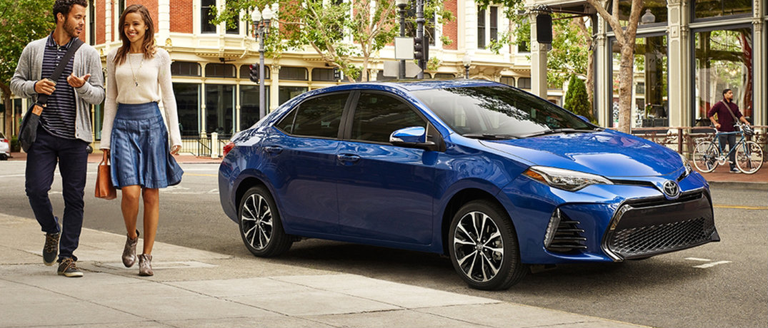 Couple walking away from their parked blue 2018 Toyota Corolla