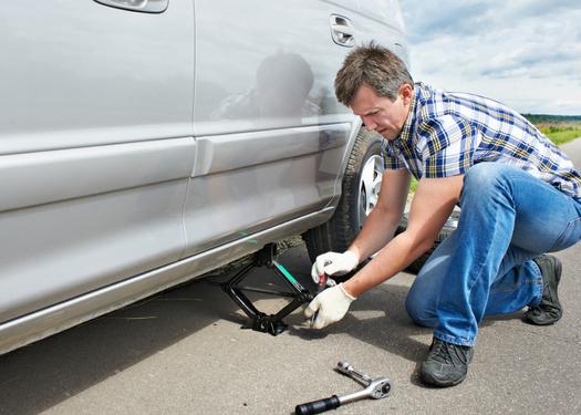 man kneeling down changing flat tire
