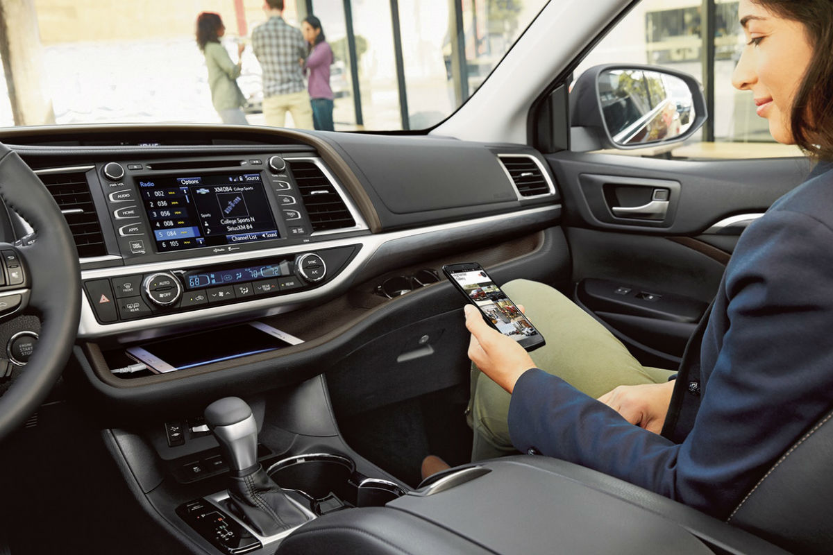 Woman syncing her phone to the touchscreen display of the 2019 Toyota Highlander