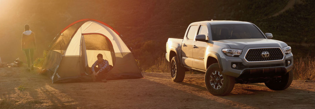 Front passenger side exterior view of a gray 2019 Toyota Tacoma parked next to a tent with the sun setting in the background