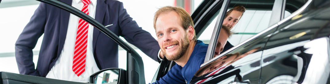Smiling customer stepping out of an efficient car after a test drive