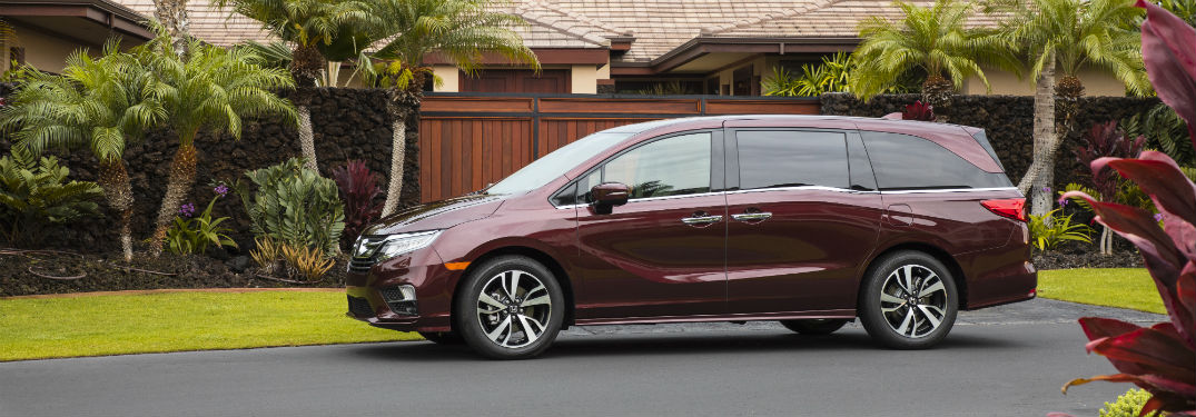 Driver side exterior view of a red 2018 Honda Odyssey