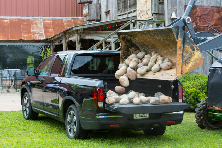 Rear exterior view of the 2019 Honda Ridgeline's bed getting filled with rocks