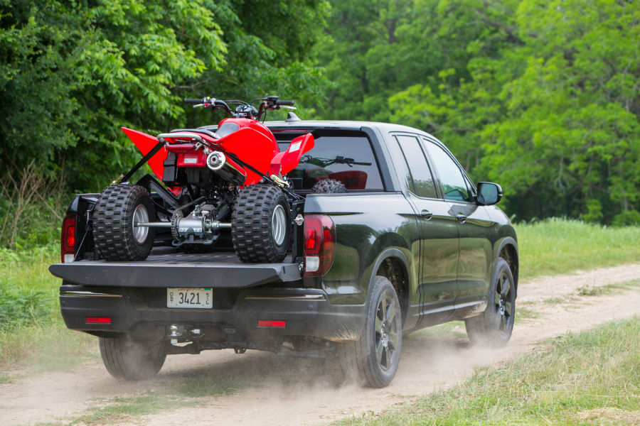 Passenger side exterior view of a 2019 Honda Riodgeline hauling a 4-wheeler in the bed