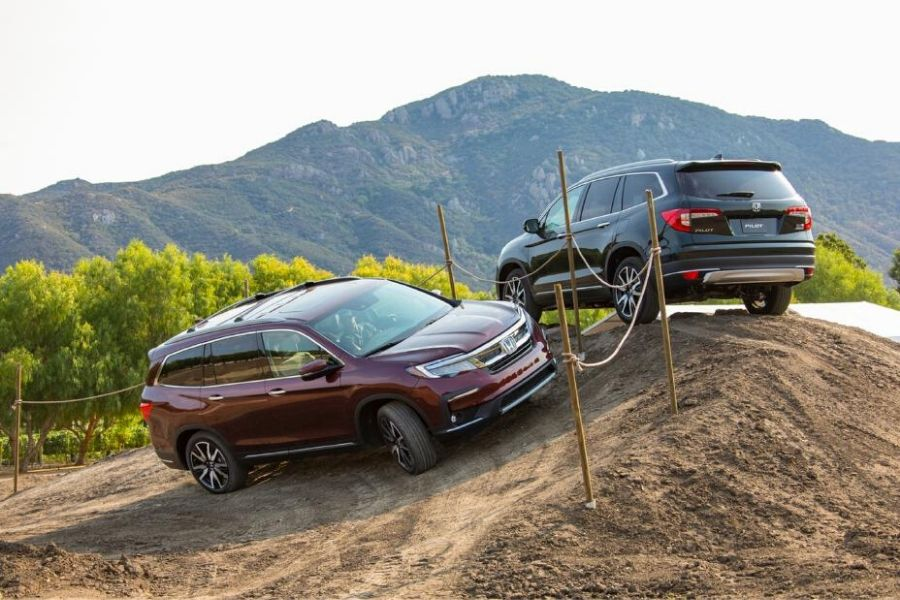 Two Honda Pilot Elites on a dirt hill from exterier front passenger and rear driver side angle