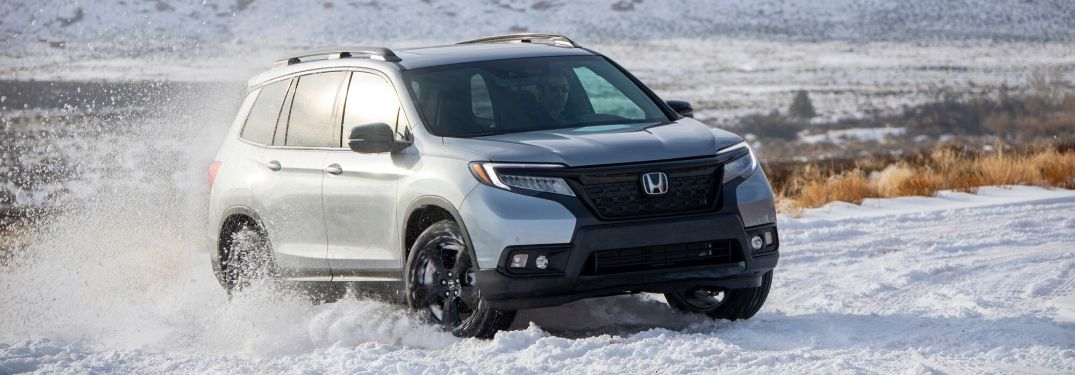 2020 Honda Passport driving through snow from exterior front passenger side
