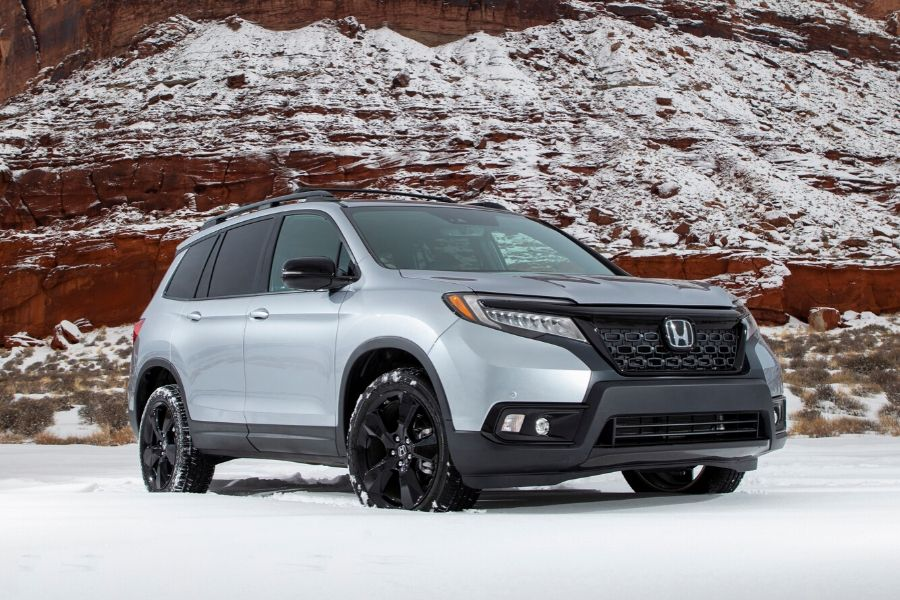 2020 Honda Passport from exterior front passenger side in front of rock and on snow