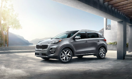 2018 Kia Sportage parked outside a luxury home's garage
