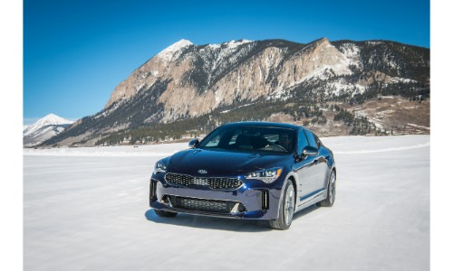 2018 Kia Stinger GT Atlantica limited edition trim level driving through a winter landscape with snowy mountains in the background