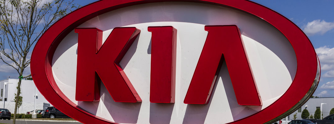 big KIA sign in the grass set outside a Kia vehicle dealership
