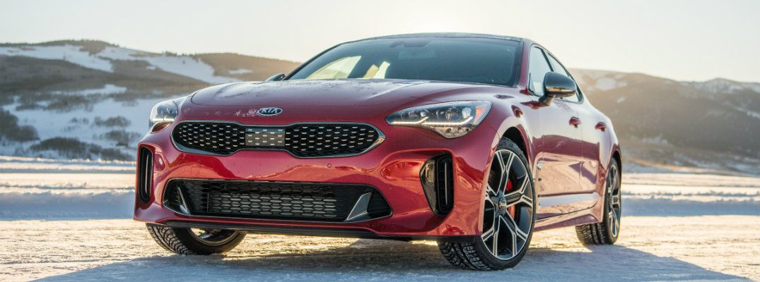 2018 Kia Stinger exterior shot parked in the snow with mountains in the background as the sun rises