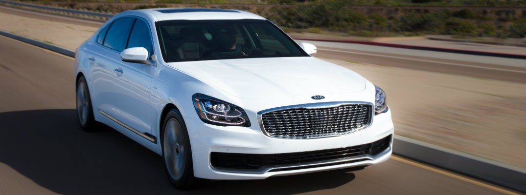 2019 Kia K900 exterior shot white driving down open highway with forest homes in the background