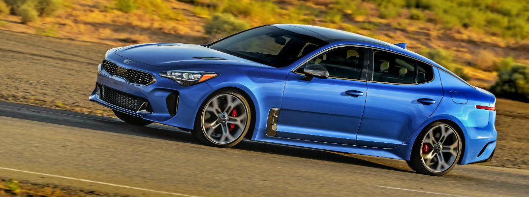 2018 Kia Stinger exterior shot angle blue paint color driving through a barren grassy wilderness
