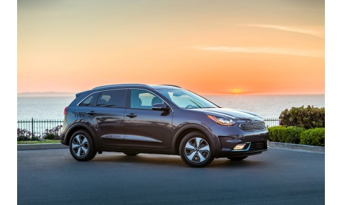 2018 Kia Niro Plug-In Hybrid gray exterior side shot by a fence near a lake with a sunset sky