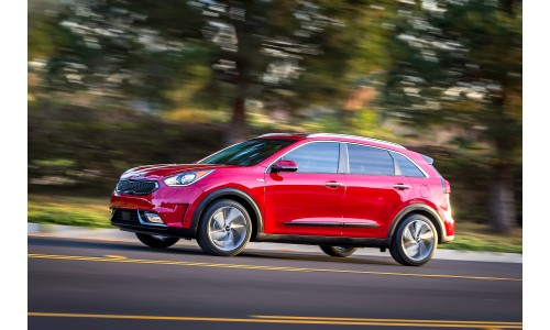 2018 Kia Niro red exterior shot driving past a blurry forest