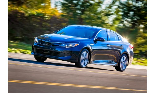 2018 Kia Optima Hybrid blue exterior shot driving by a forest with spinning wheels