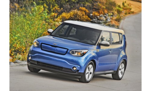 2018 Kia Soul EV blue and white exterior shot parked at an incline near bushes