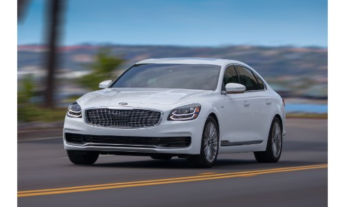 2019 Kia K900 white driving with a blurry background