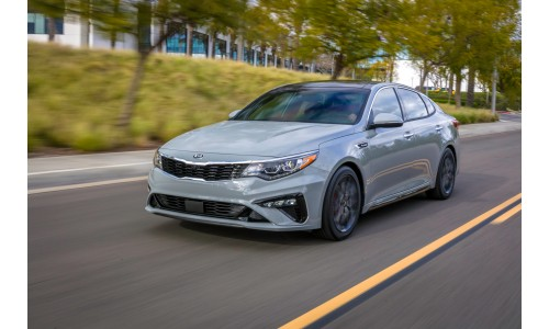 2019 Kia Optima silver driving down a forest road
