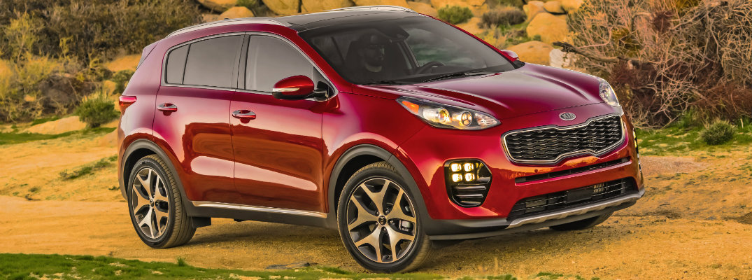 2019 Kia Sportage exterior shot hyper red paint job parked next to a rocky beach formation with a cloudy sky
