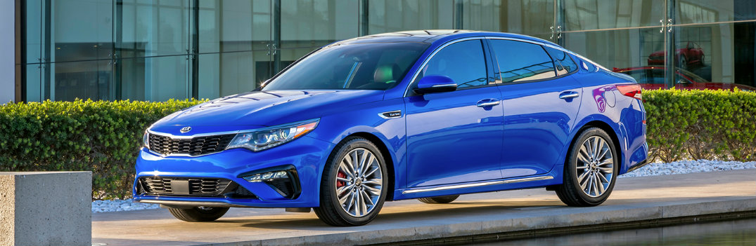 2019 Kia Optima exterior shot blue color paintjob parked outside of a kia dealership