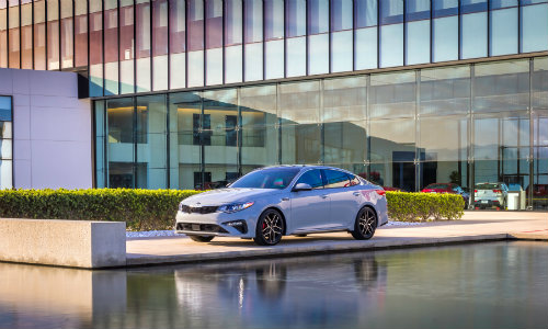 2019 Kia Optima wide exterior shot with gray color paintjob parked outside next to a luxury fountain