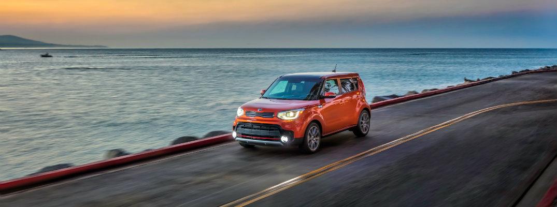 2019 Kia Soul exterior shot wild orange paint job driving alongside an ocean coast