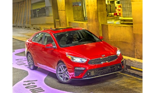 2019 Kia Forte exterior shot with red paint job driving through an underground parking garage