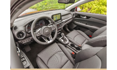2019 Kia Forte interior shot of front seating upholstery, steering wheel, and dashboard technology display