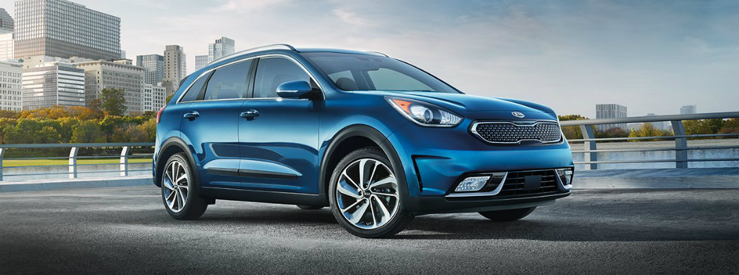 2019 Kia Niro exterior shot with light blue color paint job parked on a gravel plateau near a lake, forest, and city of skyscrapers